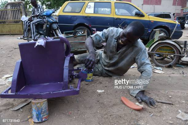 A painter and member of the Polio Victims Trust Association tries to paint a refurbished tricycle at the workshop in Kano northwest Nigeria on April...