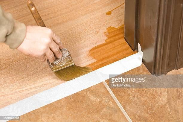 Peintre brosser clair polyuréthane sur le parquet en bois
