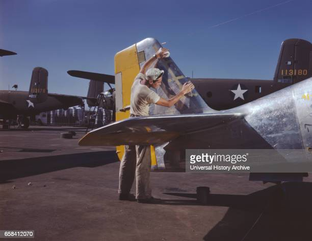 Painter Cleaning Tail Section of P51 Fighter Plane on Outdoor Assembly Line Prior to Spraying OliveDrab Camouflage of US Army North American Aviation...