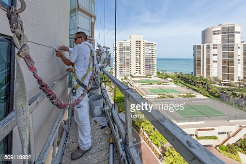 Painter Clearing the Cracks on a Highrise Building Being Prepped
