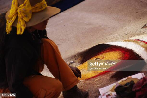 Painter drawing a face with colored dust in the street