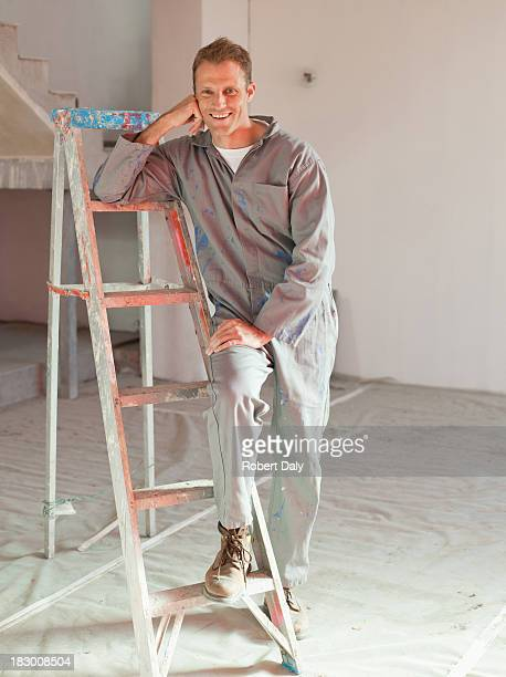 Painter in overalls leaning on ladder