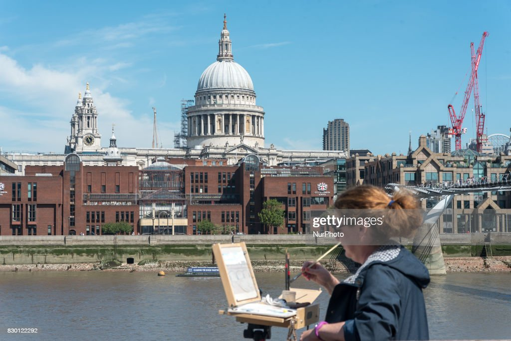 A painter is pictured while painting, against the backdrop of St. Paul's Cathedral, in a sunny morning in the Southbank of London, on August 11, 2017. The South Bank is an entertainment and commercial district of central London, next to the River Thames opposite the City of Westminster. It forms a narrow, unequal strip of riverside land within the London Borough of Lambeth and the London Borough of Southwark where it joins Bankside. As with most central London districts its edges evolve and are informally defined however its central area is bounded by Westminster Bridge and Blackfriars Bridge. It includes points of interest such as the iconic London Eye, Southbank Centre, National Theatre and Tate Modern.