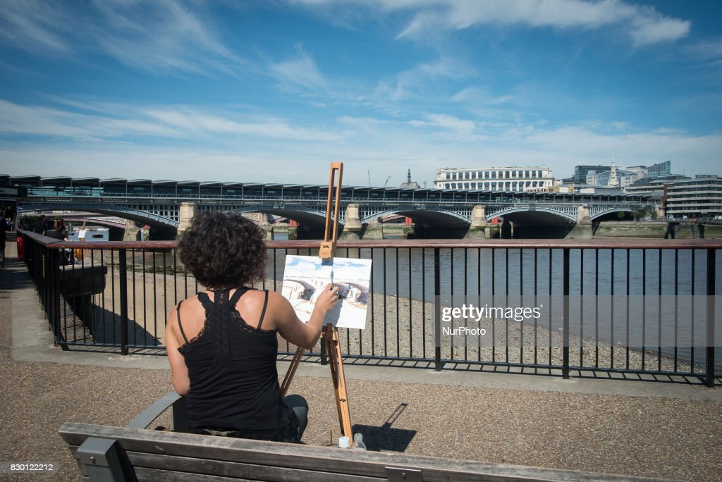 A painter is pictured while painting the Blackfriars bridge, in a sunny morning in the Southbank of London, on August 11, 2017. The South Bank is an entertainment and commercial district of central London, next to the River Thames opposite the City of Westminster. It forms a narrow, unequal strip of riverside land within the London Borough of Lambeth and the London Borough of Southwark where it joins Bankside. As with most central London districts its edges evolve and are informally defined however its central area is bounded by Westminster Bridge and Blackfriars Bridge. It includes points of interest such as the iconic London Eye, Southbank Centre, National Theatre and Tate Modern.