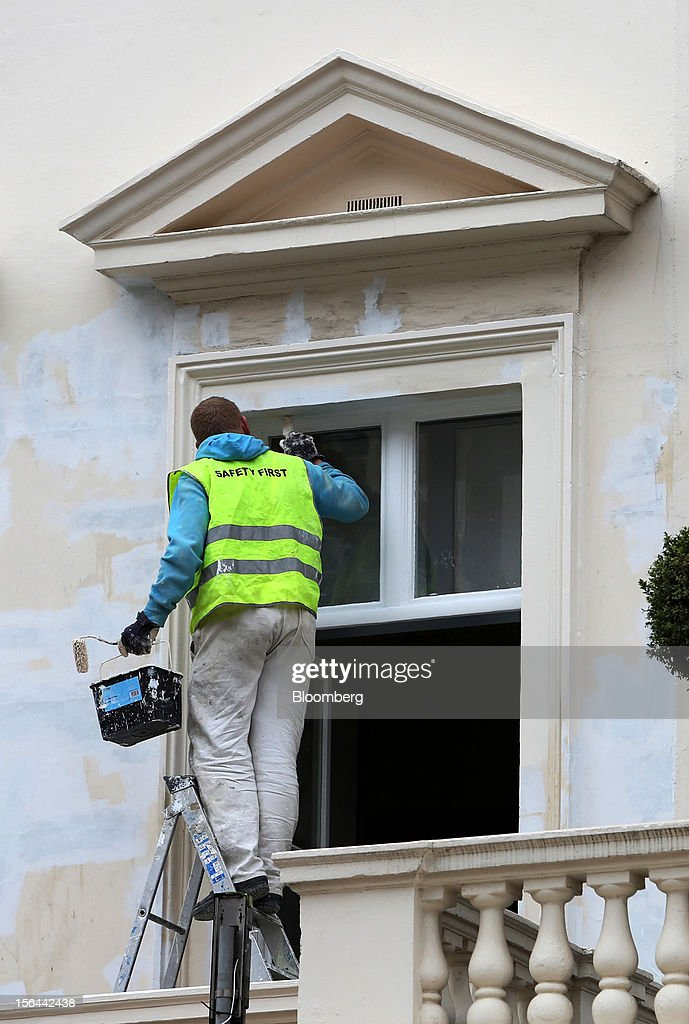A painter is seen decorating a window frame on a residential property in Eaton Place in the London area of Belgravia, in London, U.K., on Thursday, Nov. 15, 2012. London luxury homes won't rise in value next year for the first time since 2008 as proposals to extend property transaction taxes deter buyers, Jones Lang LaSalle Inc. said. Photographer: Chris Ratcliffe/Bloomberg via Getty Images