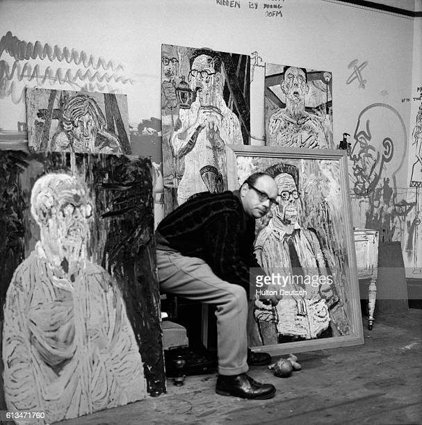 Painter John Bratby with some of his paintings from an exhibition on the effect of the explosion of a hydrogen bomb on the human figure