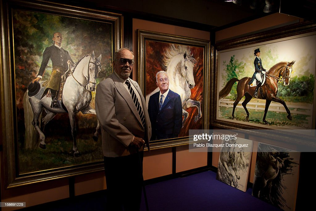 Painter Jose Carlos Gracia poses for a portrait with his pictures during Madrid Horse Week Fair at Ifema on December 23, 2012 in Madrid, Spain.