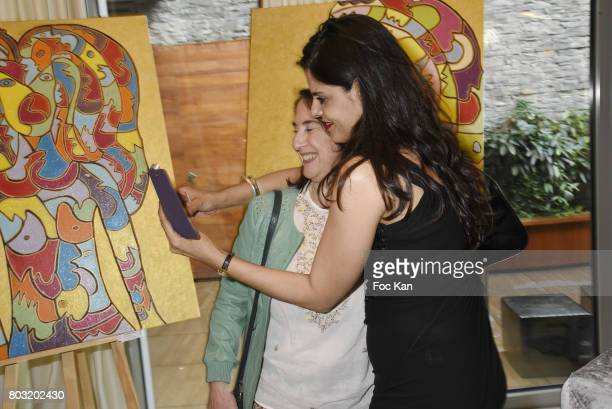 Painter Lee Michel and a guest pose for a selfie during the Dimensions Lee Michel Exhibition Preview at Hotel Rennaissance on June 28 2017 in Paris...