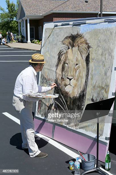 Painter Mark Balma paints a portrait of Cecil the lion to donate to antipoaching efforts in the parking lot of Dr Walter Palmer's dental clinic on...