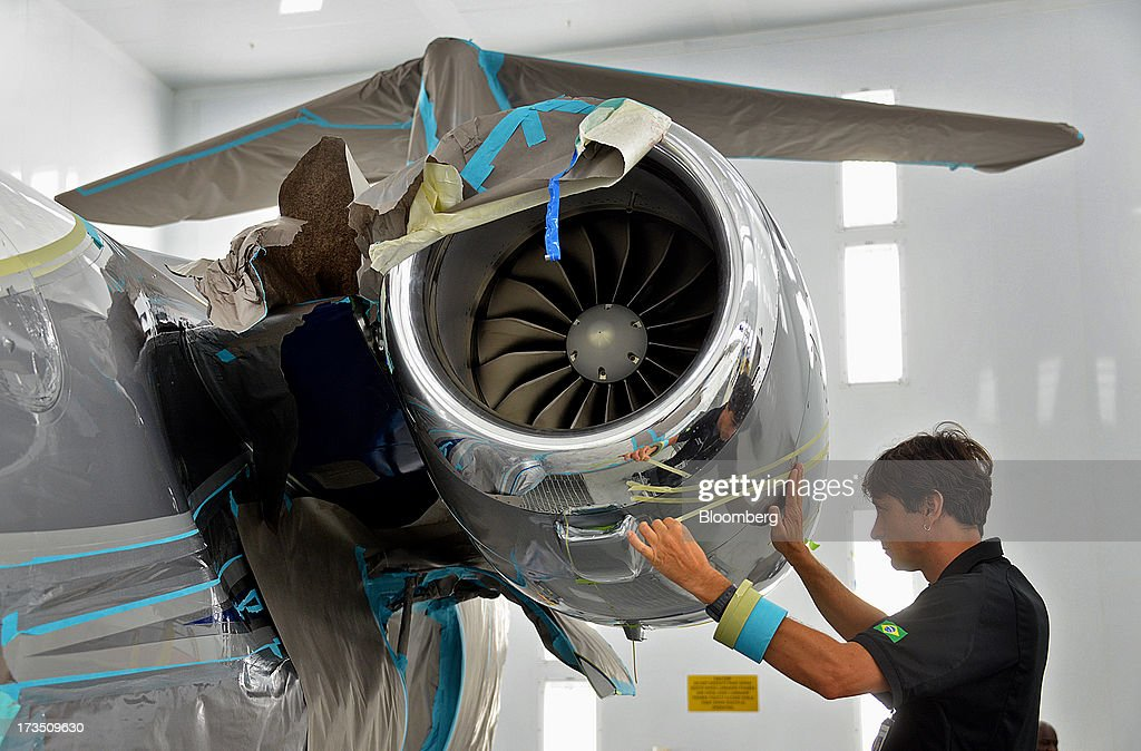 Painter Marvio Oliveira lays pinstripes on the engine cowl of an Embraer SA Phenom 100 jet at the company's executive jet manufacturing facility in Melbourne, Florida, U.S., on Monday, July 15, 2013. Embraer SA, the world's largest manufacturer of commercial jets up to 120 seats, delivered 22 jets to the commercial aviation market and 29 to the executive aviation market, for a total of 51 aircraft in the second quarter of 2013, according to a company press release. Photographer: Mark Elias/Bloomberg via Getty Images