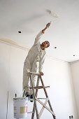 Painter painting ceiling of office