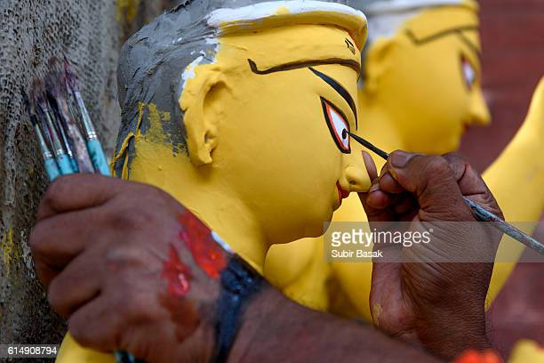 Painter painting on a statue of goddess Durga, Kolkata, West Bengal, India