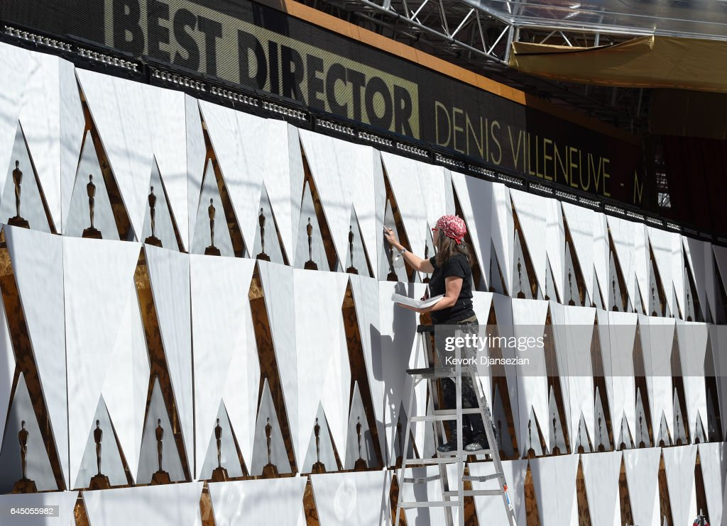 A painter puts finishing touches on a backdrop wall set up on the red carpet in preparation for the 89th Academy Awards at Hollywood and Highland Center on February 24, 2017 in Los Angeles, California.