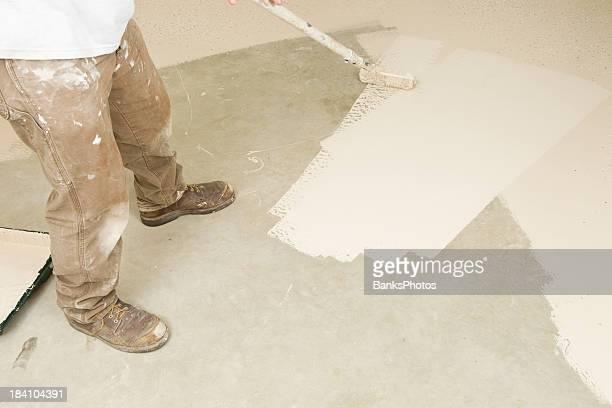 Peintre peinture rouleau Epoxy sur un sol en béton