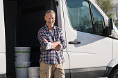 Portrait of painter standing next to his van with paint container. Decorator standing next to van and looking at camera. Happy smiling worker leaning on his white truck with folded arms.