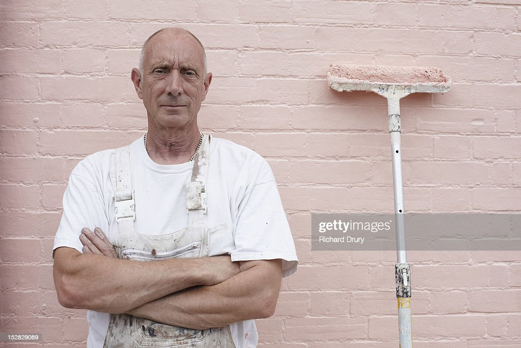 Painter standing in front of freshly painted wall