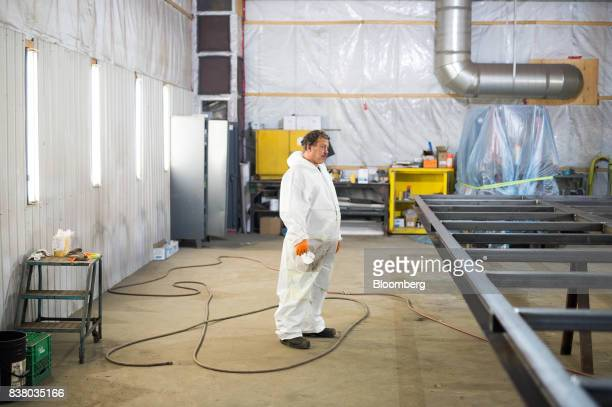 A painter stands before prepping the bottom framework of a modular farming unit at the Modular Farms Co manufacturing facility in Cornwall Ontario...