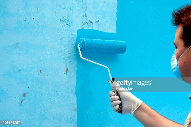 Painter wearing face mask while painting a wall bright blue