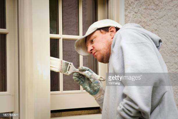 Peintre travaillant sur les encadrements de fenêtres et de peinture de l'extérieur de la maison de Maintenance