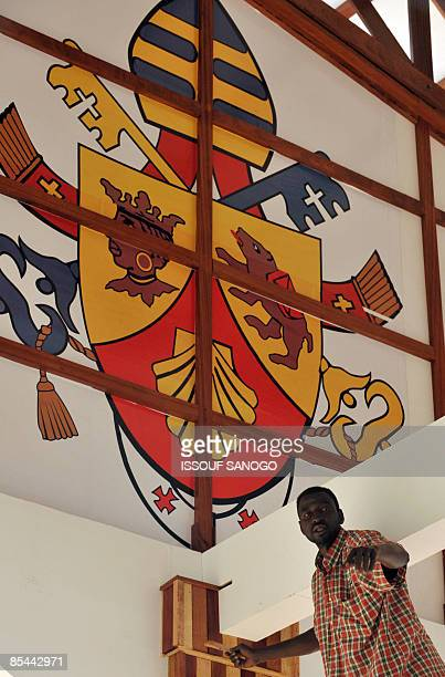 A painter works on March 16 2009 at the Amadou Ahidjo stadium of Yaounde where Pope Benedict XVI is scheduled to celebrate a mass on March 19 A buzz...