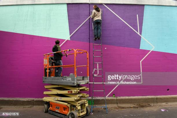 DENVER CO NOVEMBER 19 Painters Remington Robinson middle and Pat McKinney left of Sognar Creative Division work on taping sections of the wall to...