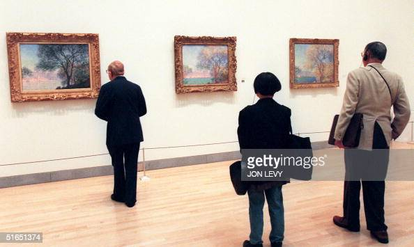 By Frederic Bichon Museum goers compare paintings by French Impressionist Claude Monet of 'Antibes Seen from La Salis' 09 October at The Brooklyn...