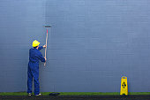 Painting a wall outside.