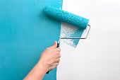 """""""A hand with a paint roller covered in teal blue paint, painting over a white wall."""""""