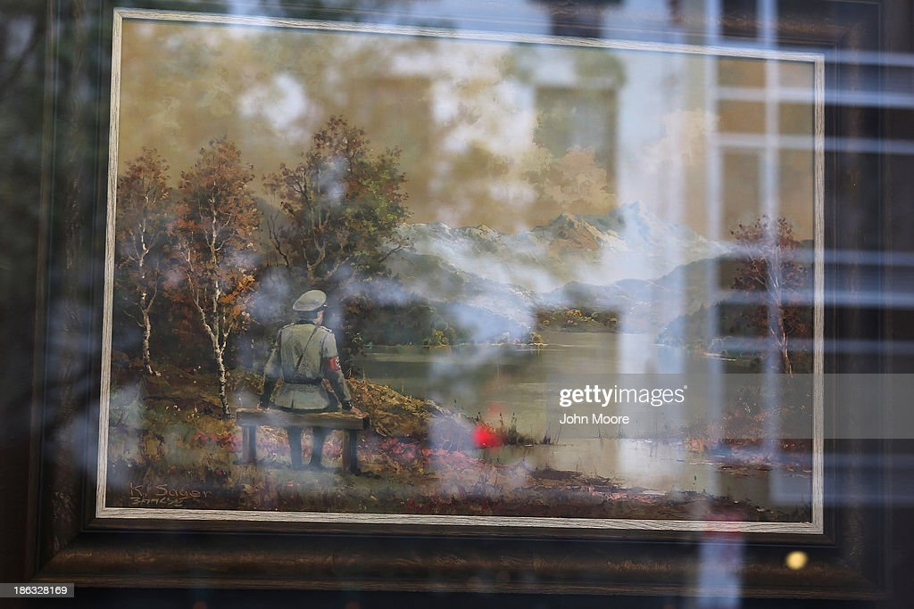 A painting, altered by British street artist Banksy, hangs on display at the Housing Works Gramercy thrift shop on October 30, 2013 in New York City. Banksy called the new piece, in which he painted a Nazi officer seated on a bench and looking over a pastoral scene, 'The banality of the banality of evil,' describing it on his website as 'a thrift store painting vandalized then re-donated to the thrift store.' The painting is currently for sale on an online auction through October 31. The money will go to charity.