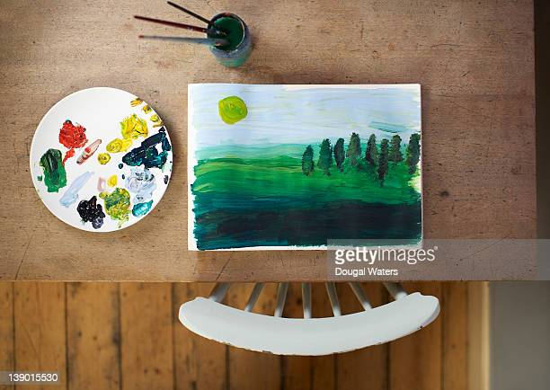 Painting and artist materials on table.