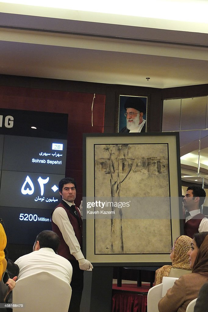 A painting by Sohrab Sepehri one of the Iranian masters is held up for the spectators under a portrait of supreme leader Ayatollah Ali Khamenei in the dinning hall of Azadi Hotel on June 28, 2013 in Tehran, Iran.