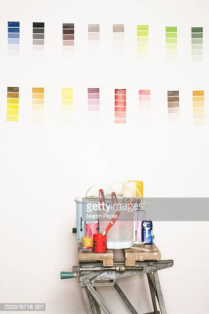 Painting equipment on workbench, colour charts on wall