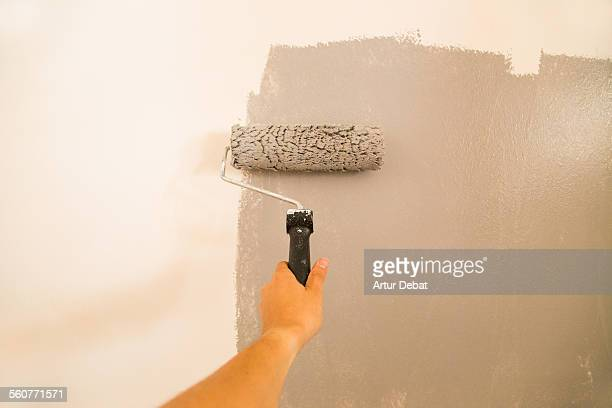 Painting home wall with paint roller from pov.