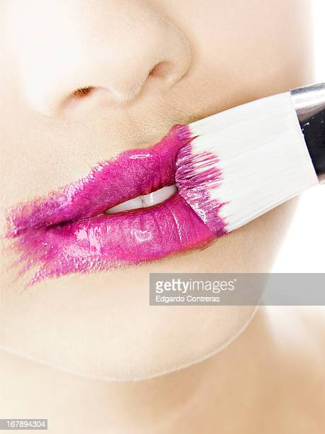 painting lips pink with a paint brush