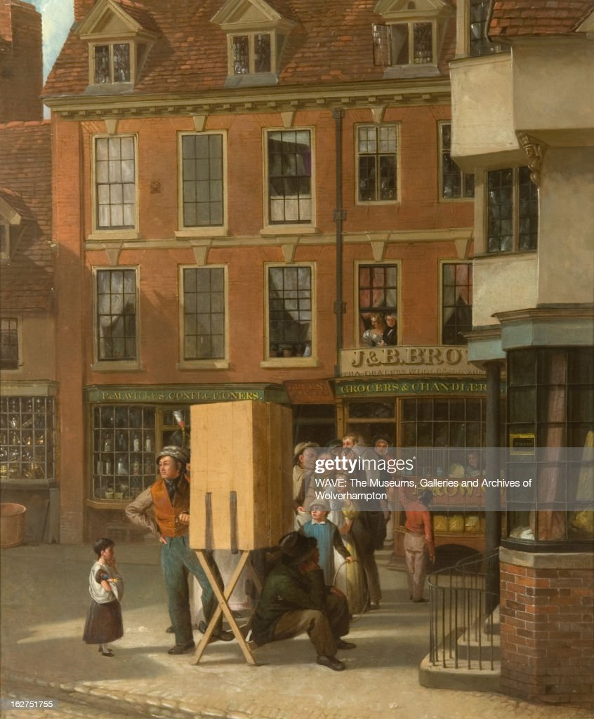 Painting of a cobbled street with red shops in the background, A group of figures stand in line behind a box on a wooden stand, To the right of the box sits a man resting his chin on his hand, On the left is a figure in an orange waistcoat, hand on hip turning a handle, while a child looks on, One of the buildings in the background has a sign 'J&B Brown', In the windows above the shops, figures look out at the street, High Green, Wolverhampton, Staffordshire, England, Britain. High Green, Wolverhampton, 1880-1889. Oil Painting by William J Pringle (fl.1805-1860).