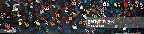 A painting of colorful handprints