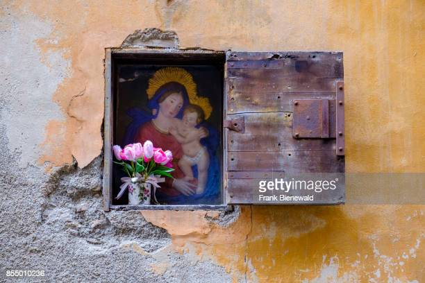 A painting of Maria and Jesus and a bunch of flowers in a niche of house wall
