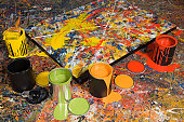 Painting on floor, surrounded by cans of paint