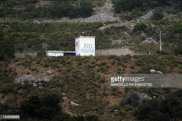 A painting reading 'No Mafia' is seen on May 16 2012 on the site where a 500kilogram bomb used in the attack which killed Judge Giovanni Falcone his...