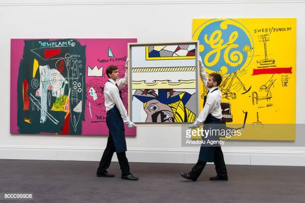 Painting titled New Flame by artists Andy Warhol and JeanMichel Basquiat with an estimate of £1000£2000 Sotheby's staff hold a painting titled Two...