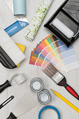 Overhead shot of painting tools including paintbrush, roller, paint tray, foam, scraper, and paint swatches plus rolls of wall paper on wooden surface