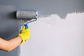 Hand in yellow glove painting wall in gray color with a roller brush.