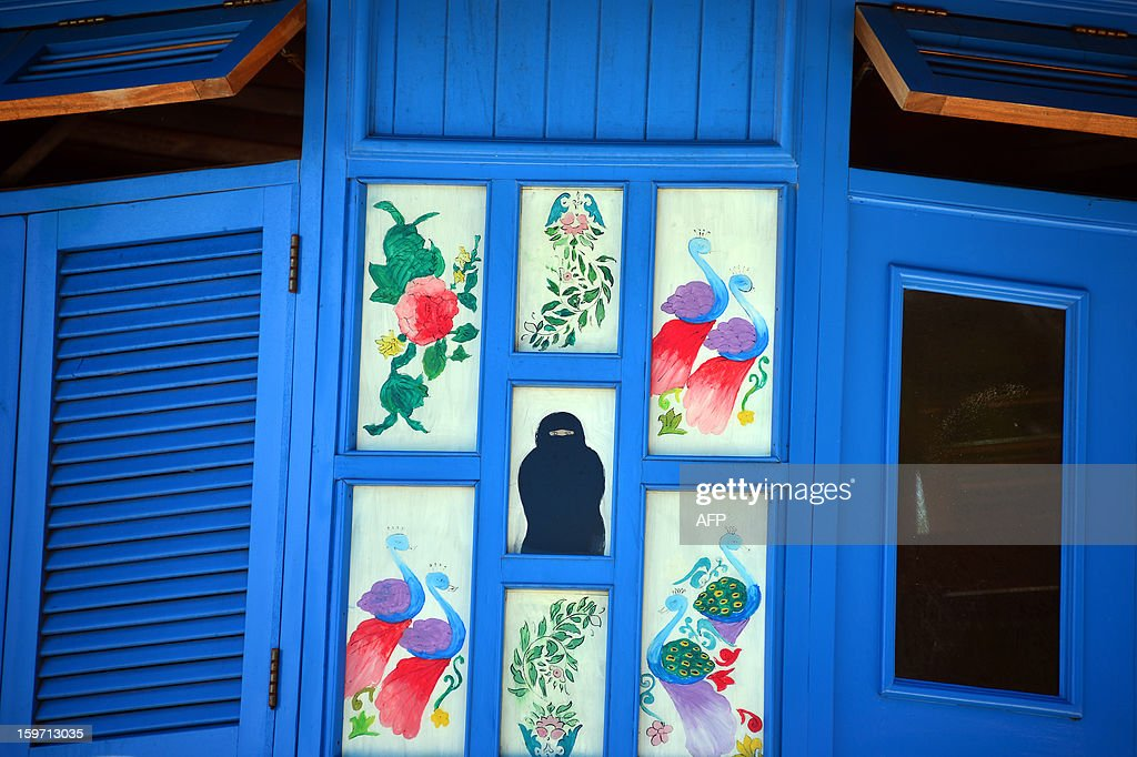 Paintings are displayed on windows of a house on January 9, 2013 in Zanzibar. AFP PHOTO / GABRIEL BOUYS