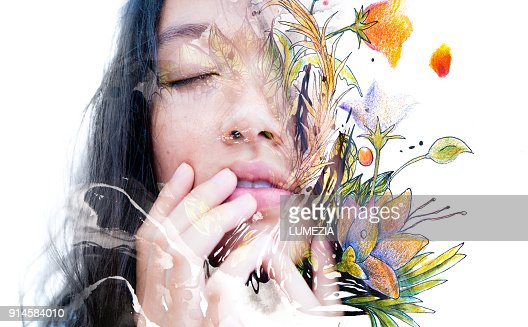 Paintography. Double exposure close-up of a sensual peaceful asian model gently touching her face combined with hand drawn ink and watercolour paintings with floral motifs : Foto stock