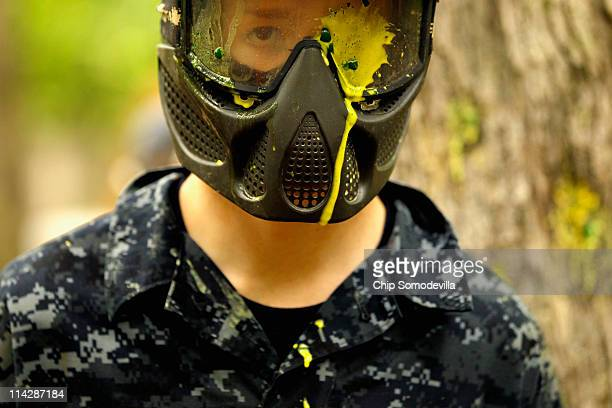 Paints drips down the mask after a member of the United States Naval Academy freshman class took a direct hit during a paintball battle as part of...