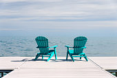 Two turqoise blue muskoka and adirondack chairs on a dock overlooking a blue lake with a sunny day blue sky