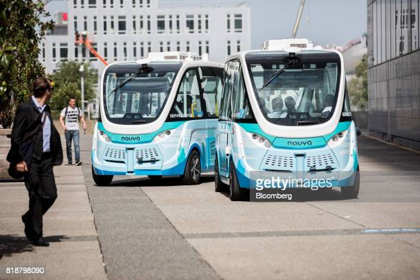 A pair of Arma autonomous shuttle buses manufactured by Navya Technologies SAS travel in La Defense business district of Paris France on Wednesday...
