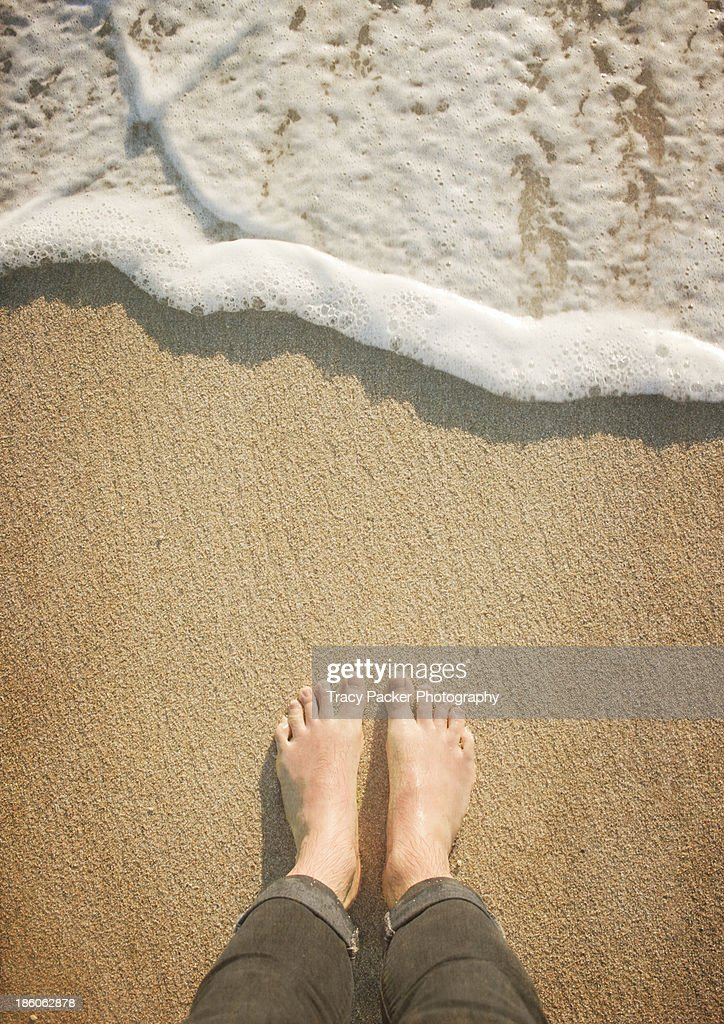 A pair of bare feet on sand await the wave