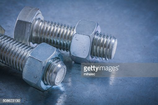 Pair of bolts and screw-nuts on metallic surface construction : Stock Photo