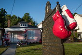 A pair of boxing gloves hang from a historical marker in front of Muhammad Ali's childhood home on Grand Ave on June 10 2016 in Louisville Kentucky...